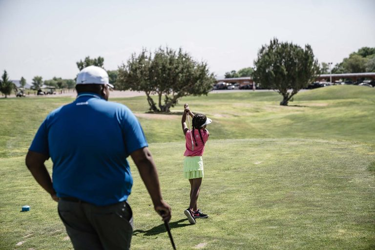 Young girl driving a golf ball while a Golf Pro watches on