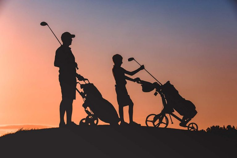 Golf Pro and child silhouetted against the morning sun