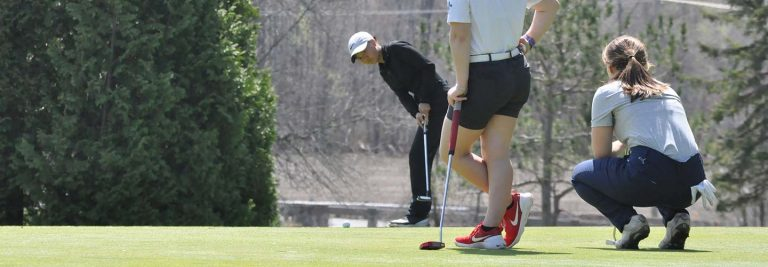 Player putting ball in hole